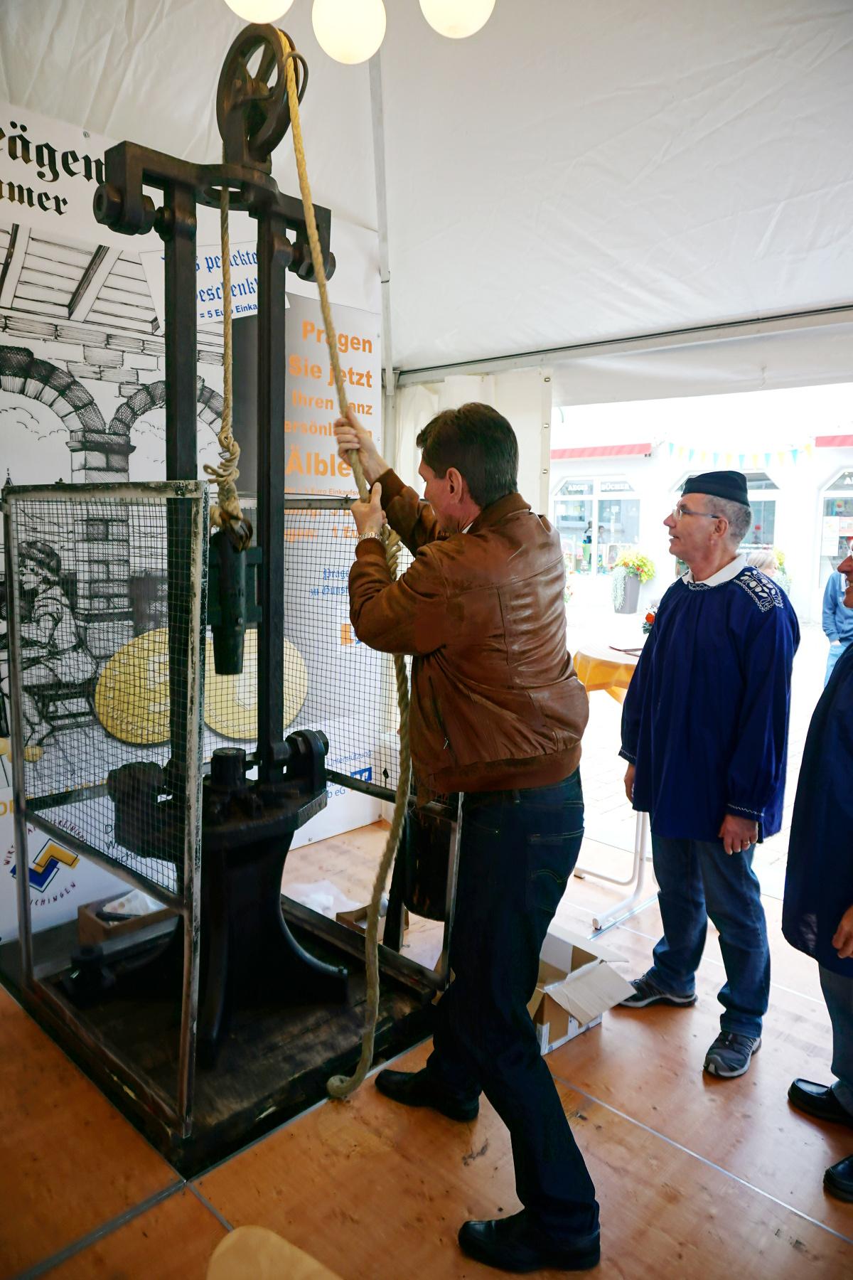 """Bürgermeister Klaus Kaufmann prägt sich am Stand der Bürgerstiftung Laichinger Alb e.V. einen """"Jubiläums-Älbler"""""""