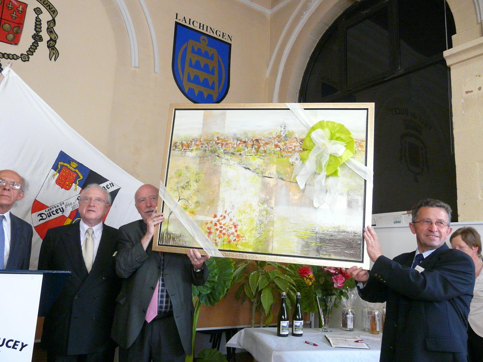 Stellvertrender Bürgermeister Martin Schwenkmezger überreicht ein Bild als Gastgeschenk mit einer Laichinger Ansicht den französischen Gästen