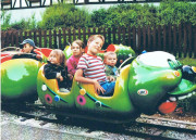 Raupenzügle Fahrgeschäft in Form einer Raupe in dem Kinder sitzen und die Kamera schauen